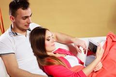 Пары используя интернет сети просматривать таблетки Стоковые Фотографии RF