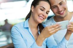 Пары используя мобильный телефон на кафе стоковое фото
