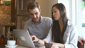 Пары используя портативный компьютер в ресторане Café сток-видео