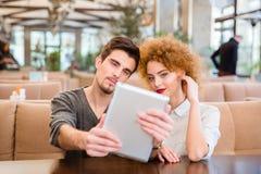 Пары используя планшет в ресторане Стоковые Фото