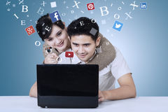 Пары используя социальный сетевой сайт на компьтер-книжке стоковая фотография