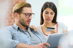 Пары используя таблетку и покупки на интернете стоковая фотография rf