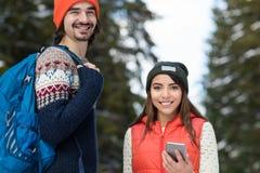 Пары используя умный телефон беседуя зима человека и женщины онлайн леса снега счастливая усмехаясь идя внешняя Стоковое Изображение RF