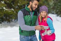 Пары используя умный телефон беседуя зима человека и женщины онлайн леса снега счастливая усмехаясь идя внешняя Стоковые Изображения
