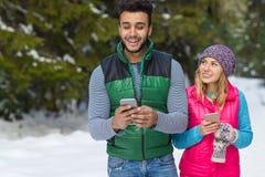 Пары используя умный телефон беседуя зима человека и женщины онлайн леса снега счастливая усмехаясь идя внешняя Стоковая Фотография