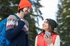 Пары используя умный телефон беседуя зима человека и женщины онлайн леса снега счастливая усмехаясь идя внешняя Стоковая Фотография RF