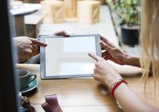 Пары используя цифровую таблетку в кафе Стоковое Фото