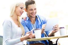 Пары используя цифровую таблетку на кафе Стоковое фото RF