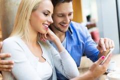 Пары используя цифровую таблетку на кафе Стоковая Фотография