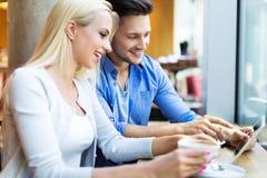 Пары используя цифровую таблетку на кафе Стоковые Изображения