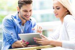 Пары используя цифровую таблетку на кафе Стоковое Изображение RF
