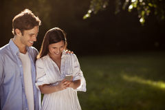 Пары используя smartphone в парке Стоковое Фото