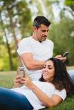 Пары используя smartphone для отправки СМС во время даты на парке Стоковое Изображение