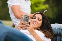 Пары используя smartphone для отправки СМС во время даты на парке Стоковое Изображение RF