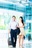Пары идя в лобби гостиницы с чемоданом стоковые фото
