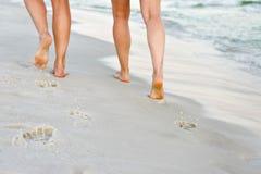 Пары идя вдоль песчаного пляжа Стоковая Фотография