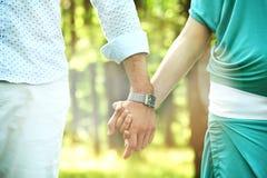 Пары идя держащ влюбленность рук Стоковые Фото