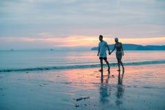 Пары идя держащ руки на пляже на заходе солнца, молодом туристском человеке и женщине на празднике моря стоковая фотография