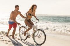 Пары идя на велосипед едут на пляже Стоковые Фото