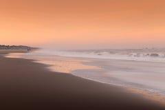 Пары идя на пляж на заходе солнца Стоковая Фотография RF