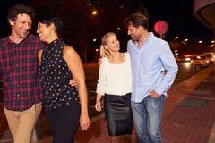 2 пары идя через городок совместно на ночу Стоковые Фото
