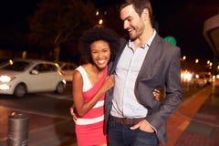 Пары идя через городок совместно на ночу Стоковые Изображения RF