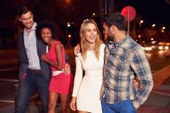 2 пары идя через городок совместно на ночу Стоковая Фотография