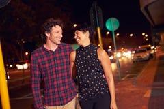 Пары идя через городок совместно на ночу Стоковая Фотография RF