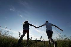 Пары идя через поле стоковое фото rf