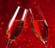 Пары каннелюр шампанского на предпосылке bokeh красного света Стоковое Изображение