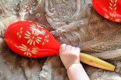 Пары красных деревянных maracas и руки младенца Стоковые Фото
