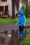 Пары красочных резиновых ботинок в большой лужице Мальчик имея потеху после дождя напольно стоковое изображение rf