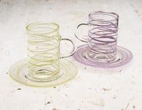 Пары кристаллических чашек с соответствуя поддонниками на каменной поверхности Стоковая Фотография RF