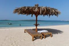 Пары кроватей солнца и парасоль на песчаном пляже Стоковая Фотография