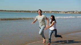Пары летних каникулов пляжа бежать на праздниках Счастливые каникулы пляжа потехи соединяют идти совместно смеющся над имеющ поте акции видеоматериалы