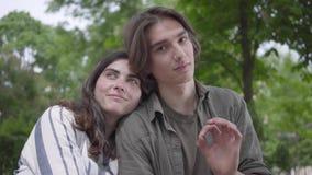 Пары любов портрета милые в случайных одеждах тратя время совместно в парке, имеющ дату Любовники сидя на акции видеоматериалы