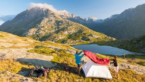 Пары людей настраивая располагаясь лагерем шатер на горах, промежуток времени Лето рискует на Альпах, идилличном озере и саммите Стоковая Фотография RF