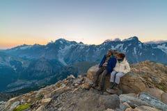 Пары людей смотря восход солнца над горным пиком Монблана 4810 m Аоста ` Valle d, итальянские приключения лета и trav стоковые изображения