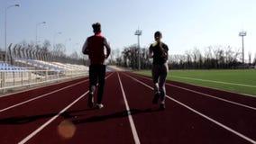 Пары мальчика девушки пригонки детенышей довольно активные тренируя совместно разрабатывать outdoors jogging идущее снаружи на бо акции видеоматериалы