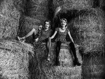 Пары молодого сексуального лесбосского laught девушек в платьях и чулках света flirt, играют в выгоне в сеновале в лете Стоковая Фотография