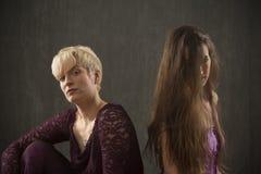 Пары молодых женщин в платьях сидя в студии Стоковое фото RF