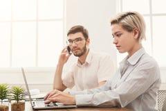Пары молодых коллег работают на современном офисе Стоковые Изображения