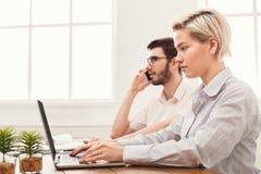 Пары молодых коллег работая на современном офисе Стоковое Изображение RF
