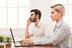 Пары молодых коллег работая на современном офисе Стоковые Фотографии RF