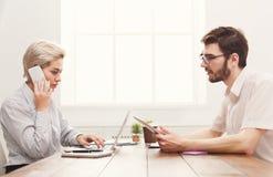 Пары молодых коллег работая на современном офисе Стоковые Изображения