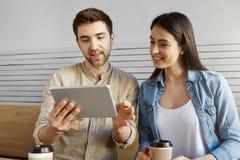 Пары молодых enterpreners сидя в кафе работая на новом startup проекте Гай показывая статистик вебсайта на цифровом Стоковые Фотографии RF