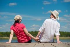 Пары молодые люди на пристани смотря природу Стоковое фото RF