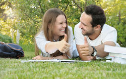 Пары молодых студентов имеют потеху пока studing в парке Стоковое Изображение RF