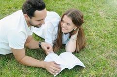 Пары молодых студентов читая книгу и studing совместно внутри Стоковые Изображения