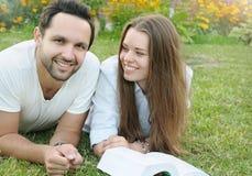 Пары молодых студентов читая книгу совместно в парке Стоковые Фото